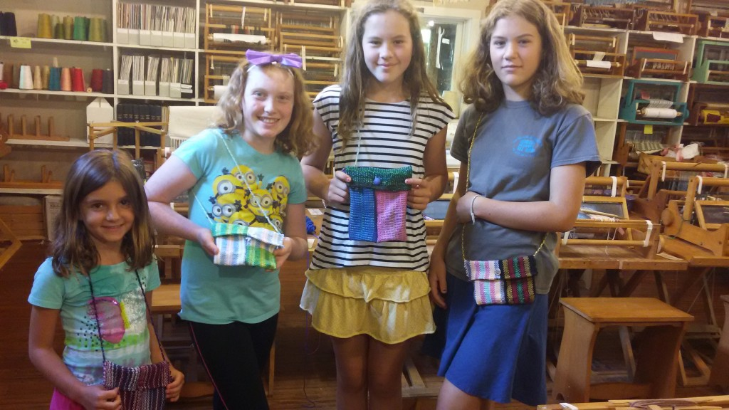 Four Young Students show off their purses made in the Weaving Wednesday Class on August 12. Students were asked to focus on color and pattern as they wove. Teacher, Michelle Amos, machine pieced the bags as students braided straps and picked out button clasps. As you can see, the students were very proud of their creations.